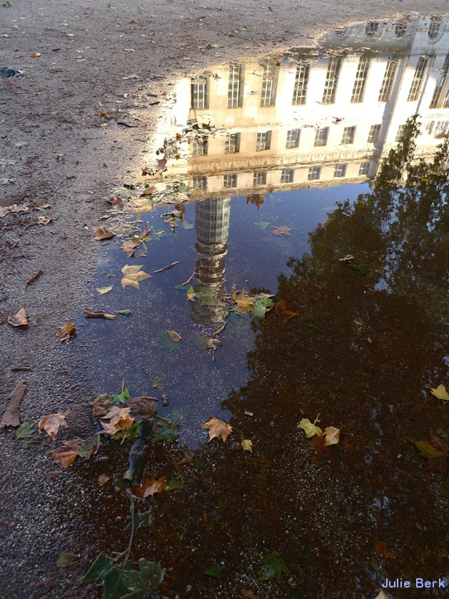 Post Office Tower reflected in puddle in Fitzroy Square